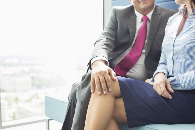 Midsection-of-businessman-flirting-with-female-colleague-in-office