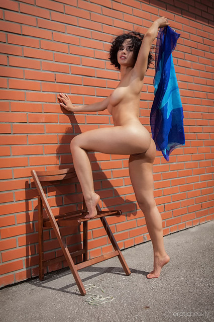 pammie-lee-poses-naked-by-the-wall-showing-off-her-knockers-05