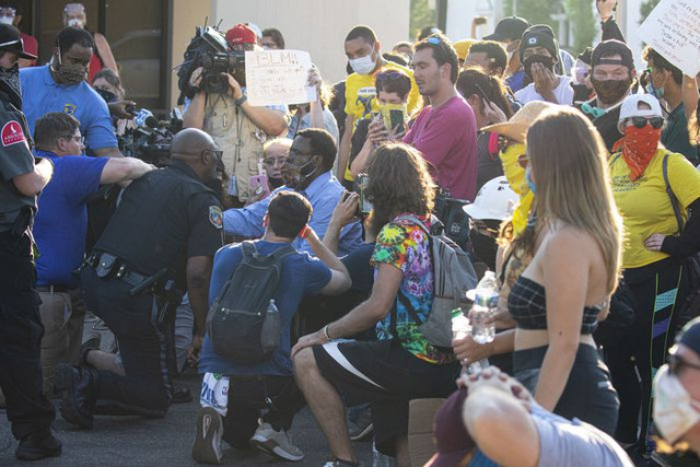Public Safety Assistant Chief of Operations, Vernon Coakley, takes a knee as he tries reasons with protesters to go home after violating curfew as they gather in the intersection of Park Street and West Michigan Avenue in downtown Kalamazoo, Michigan on Tuesday, June 2, 2020. The City of Kalamazoo imposed a curfew from 7 p.m. until 5 a.m. on Wednesday, June 3 after late night vandalism the morning before.  https://www.mlive.com/news/kalamazoo/2020/06/my-heart-was-wrenched-with-pain-assistant-chief-says-of-ordering-tear-gas-on-protesters.html