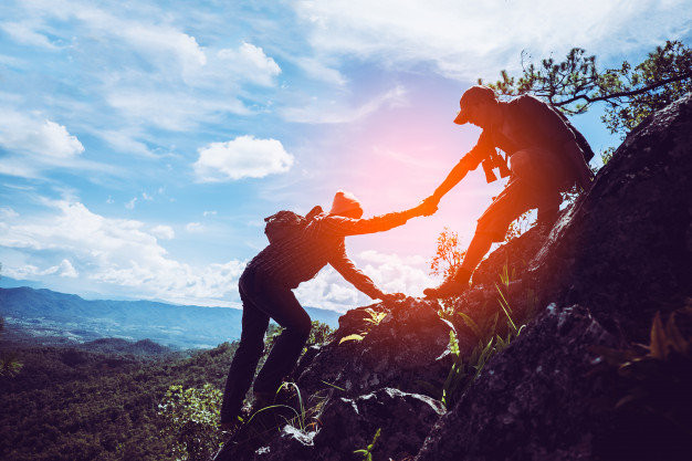 Two friends helping each other with teamwork trying reach top mountains 2379 1741