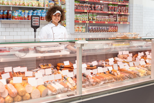 Front-view-of-cheerful-girl-posing-behind-store-counter-fresh-meat-products-in-refrigerator-Portrait