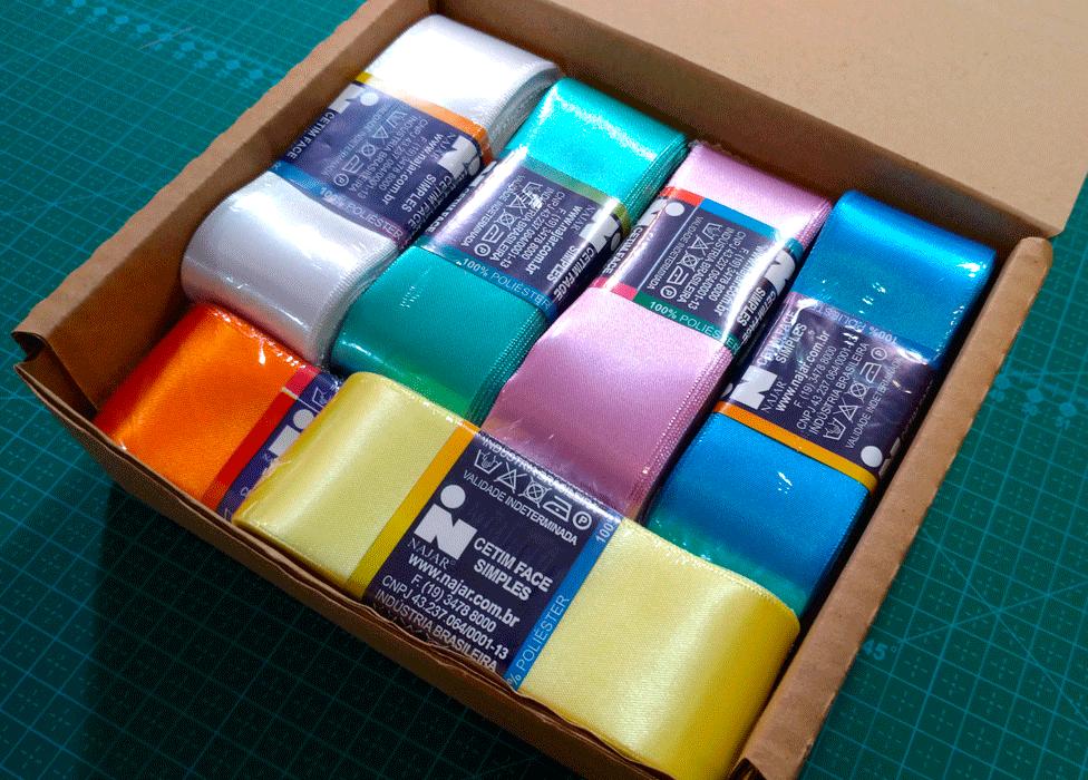 Imagem mostra uma caixa contendo fitas de cetim, pronta para ser enviada pelos Correios.
