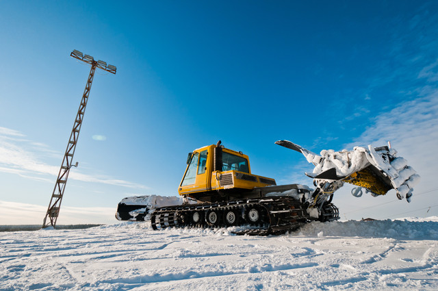 Yellow-snowcat-standing-on-top-of-the-mountain
