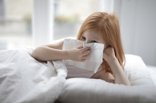sick-little-girl-blowing-nose-with-tissue-lying-in-bed-3887616