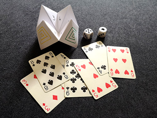 An image of a fan of cards, two dice, and a paper fortune teller.