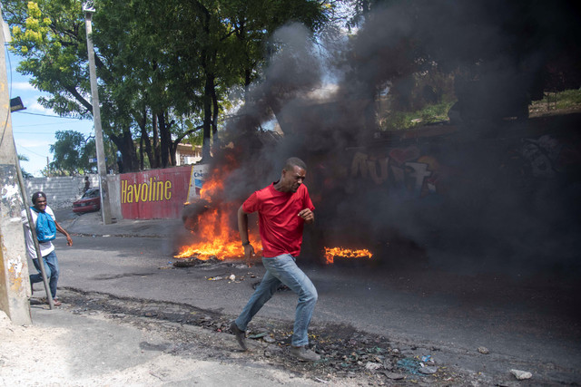 epa07365795-A-person-rans-pass-a-burning-blockade-during-a-protest-in-Port-au-Prince-Haiti-12-Februa