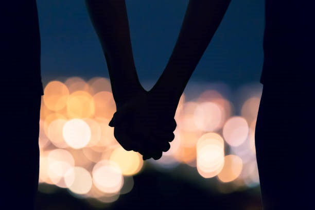 Couple-holding-hands-against-city-night-lights