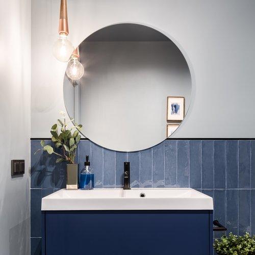 round mirror over navy bathroom sink