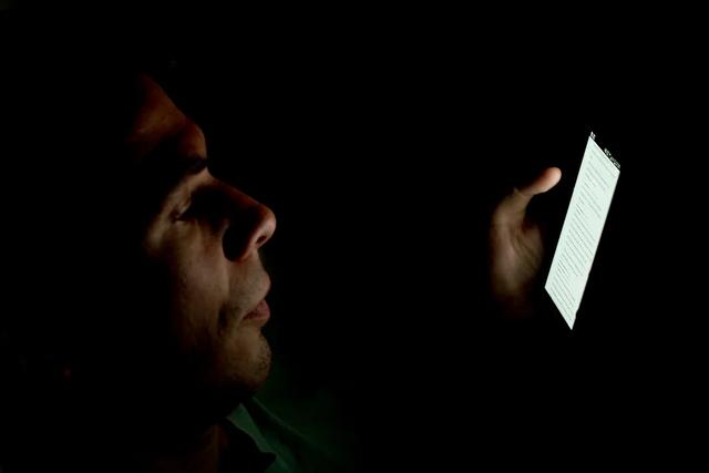 человек читает телефон ночью