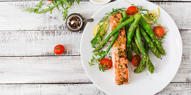 Baked-salmon-garnished-with-asparagus-and-tomatoes-with-herbs-Top-view
