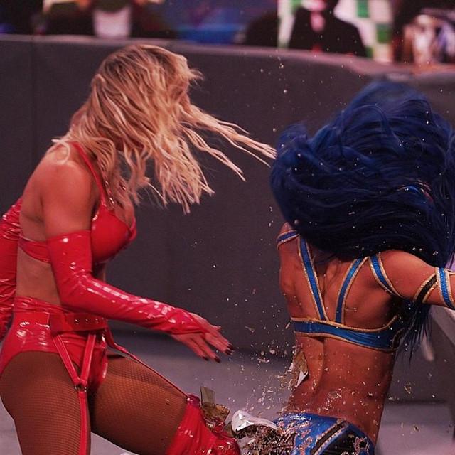 Carmella rompe una botella con Sasha Banks