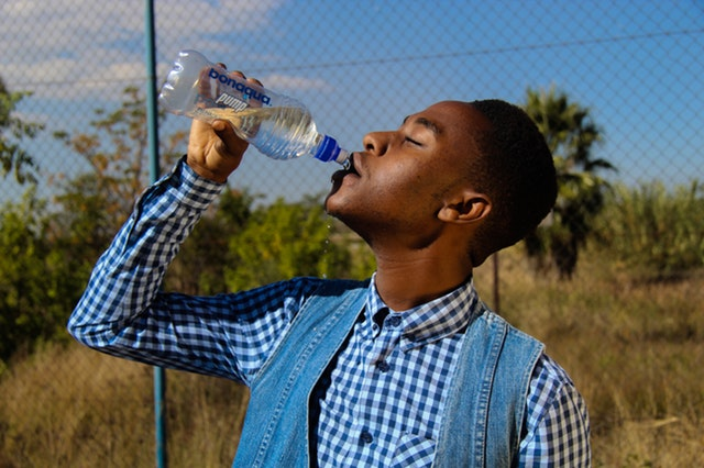 Photo of a man outdoors drinking from a bottle of water.