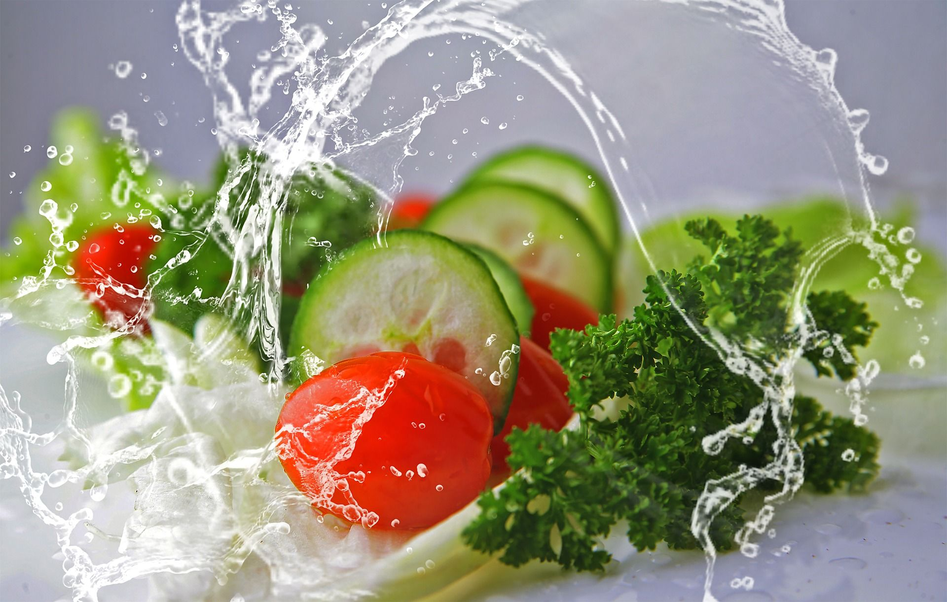 water splashing on baby tomato, cilantro with cucumber slices.
