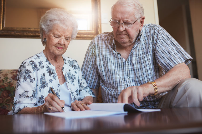 Indoor-shot-of-mature-couple-at-home-signing-documents-together-Senior-man-and-woman-sitting-on-sofa