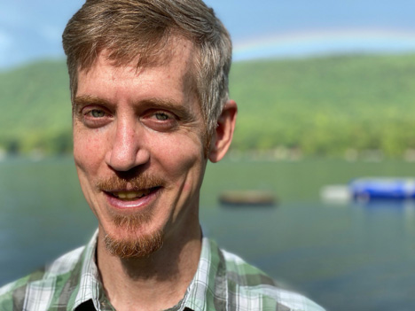 Dan fitzferald author photo. Author is smiling at the camera; behind Dan, a very characteristic nature background with a river and a hill and hey, is that a rainbow?!