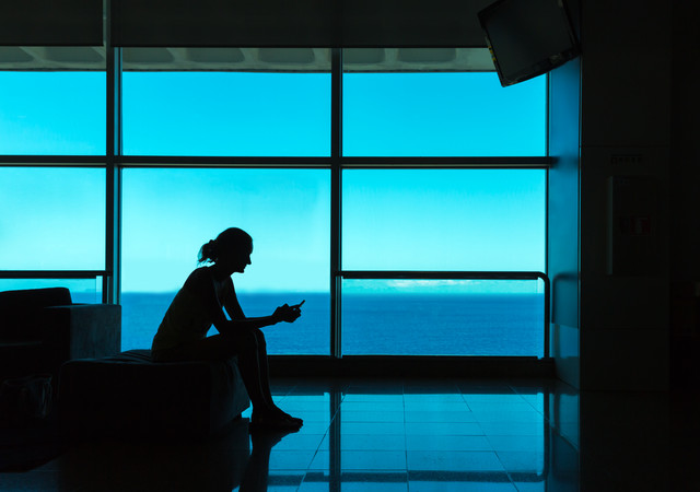 Silhouette-of-woman-with-cell-phone-against-the-window
