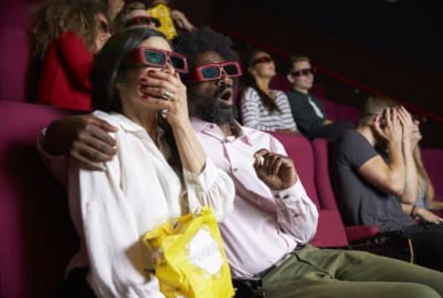 Люди смотрят ужасы в кинотеатре