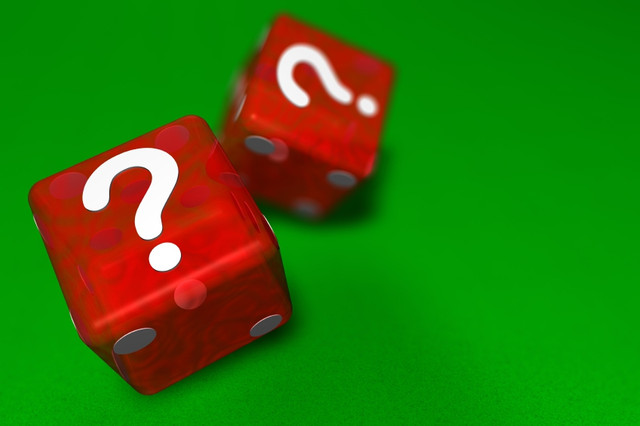 Two-red-casino-dice-landing-question-mark-sided-up-on-green-cloth-suggesting-mystery-with-shallow-de