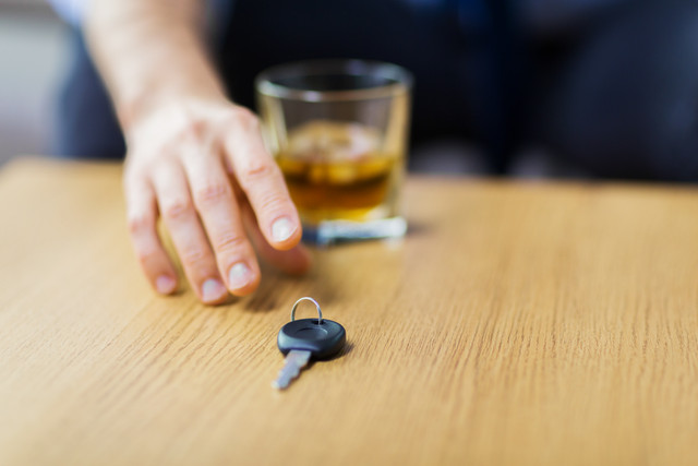 alcohol-abuse-drunk-driving-and-people-concept-close-up-of-male-driver-hand-with-whiskey-glass-takin