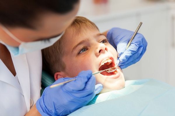dentist-examining-boys-teeth-close-up