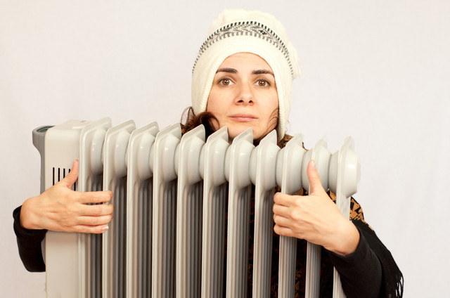 Woman-freezing-near-the-heater-i-Stock-000046326118-Small