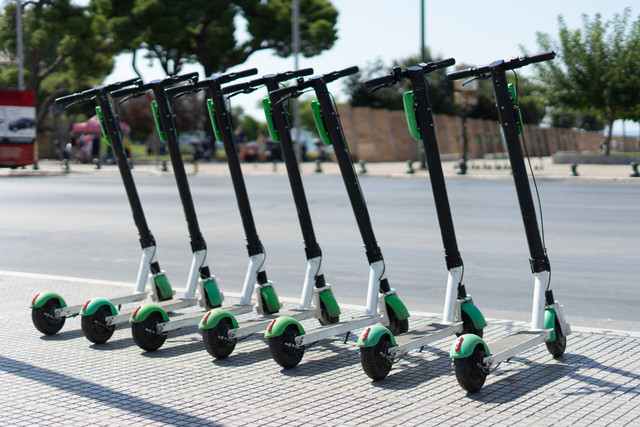 Lime-Electric-push-kick-scooter-sharing-rentals-in-sunny-day-by-in-a-row-scooters-by-the-street-on-t
