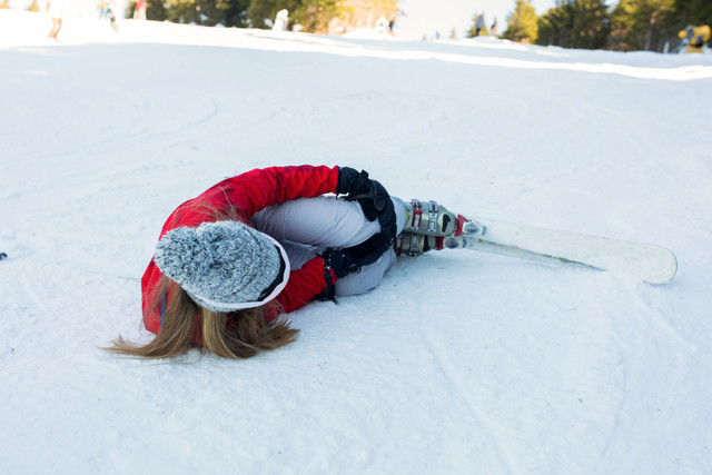 Teenager-girl-lying-on-snow-at-ski-slope-and-holding-her-leg-in-pain