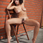 pammie-lee-poses-naked-by-the-wall-showing-off-her-knockers-15