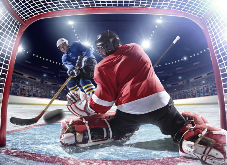 Inside-gates-view-of-professional-ice-hockey-player-scoring-during-game-in-indoor-arena-full-of-spec
