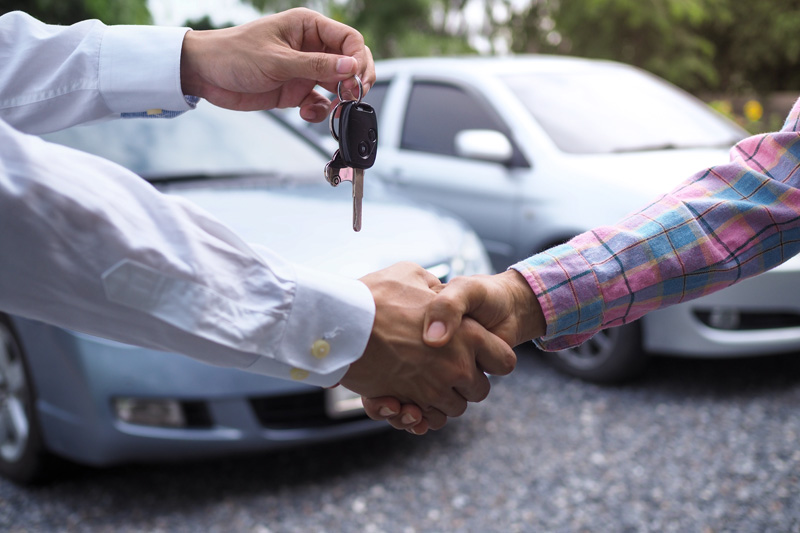 The-car-salesman-is-handing-over-the-keys-to-the-buyer-after-the-lease-has-been-agreed