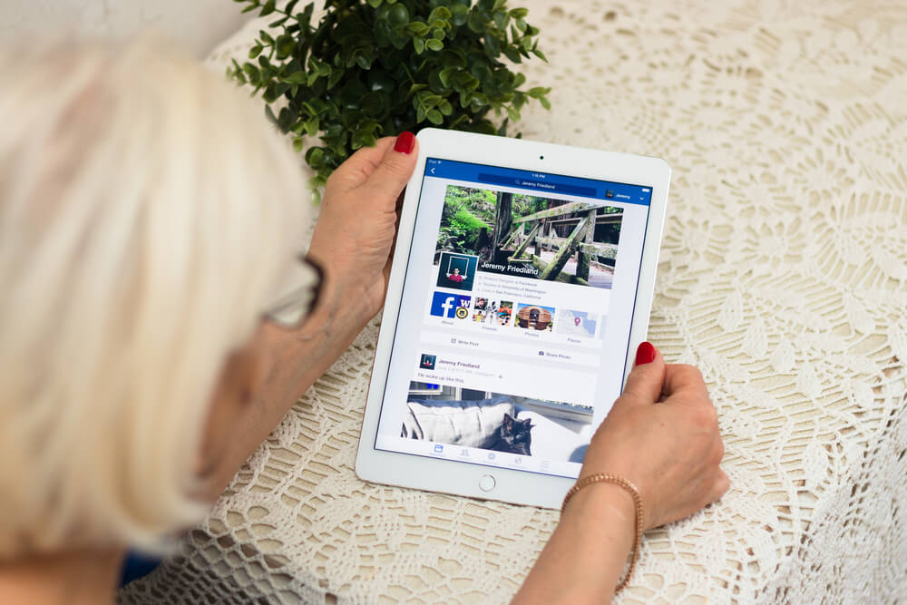lady accessing facebook publications via tablet