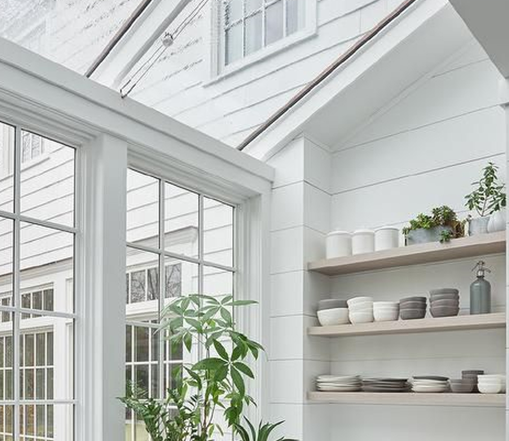 Morgan Harrison Home - Under a glass ceiling positioned over a dark stained wood floor, a white kitchen pantry boasts white shaker cabinets fited with polished nickel pulls and a white quartz countertop.