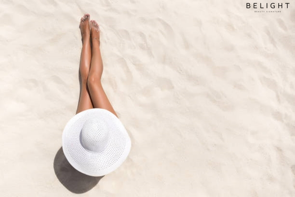 Summer-holiday-fashion-concept-tanning-woman-wearing-sun-hat-at-the-beach-on-a-white-sand-shot-from-.jpg