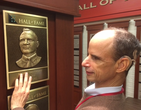 A man with dark brown receding hair touches a bronze plaque with a picture.