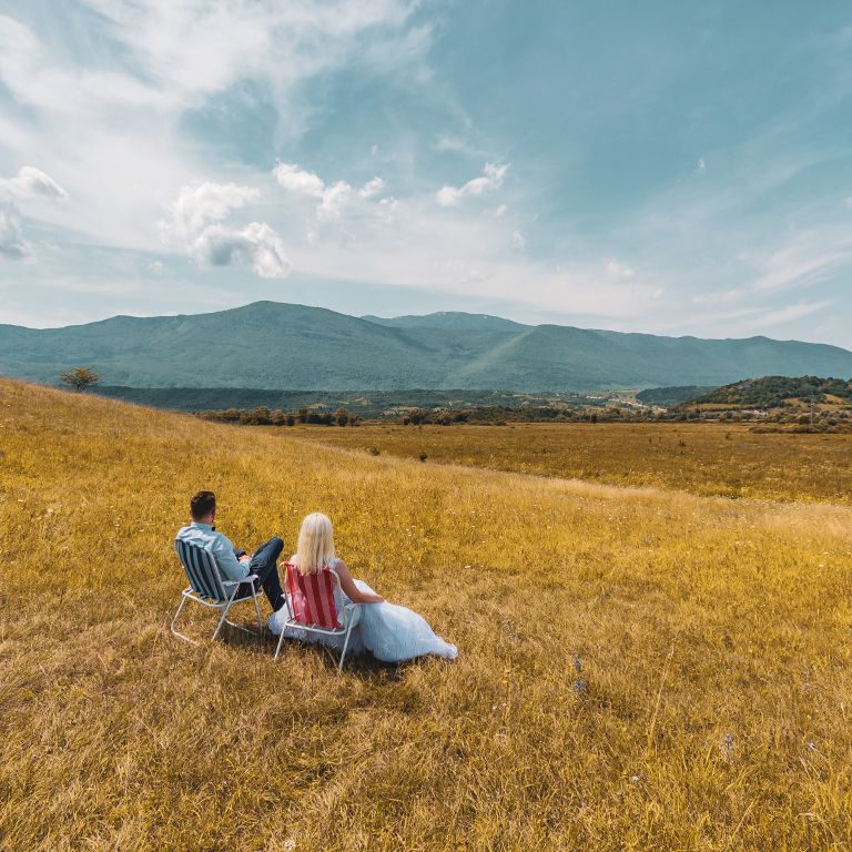 Nedžad and Erna sitting on chairs in field
