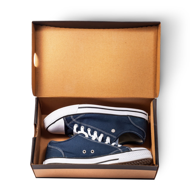 Dark-blue-sports-shoes-inside-cardboard-box-isolated-on-white-background