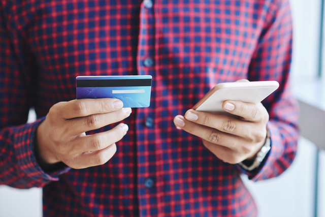 Hands-of-man-making-online-purchases-with-smartphone-and-credit-card