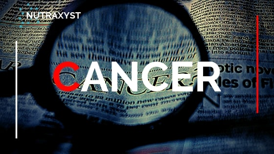 "Cancer. newspaper with text ""cancer"" being magnified by a magnifying glass."