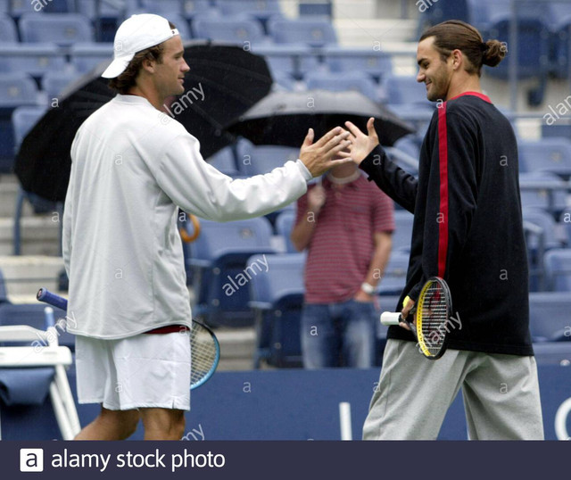 roger-federer-r-of-switzerland-and-carlos-moya-of-spain-shake-hands-after-hitting-a-few-balls-on-cen