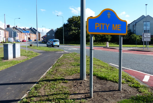 An image of the village sign for Pity Me.