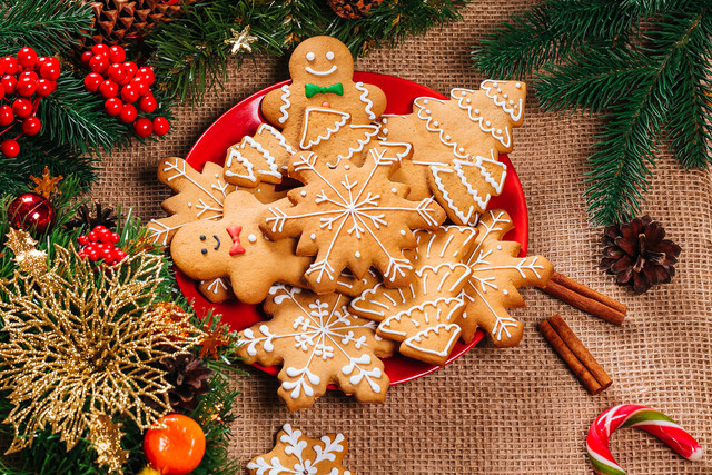 Christmas-gingerbread-cookies-homemade-in-red-plate-with-branches-of-Christmas-tree-and-New-Year-dec