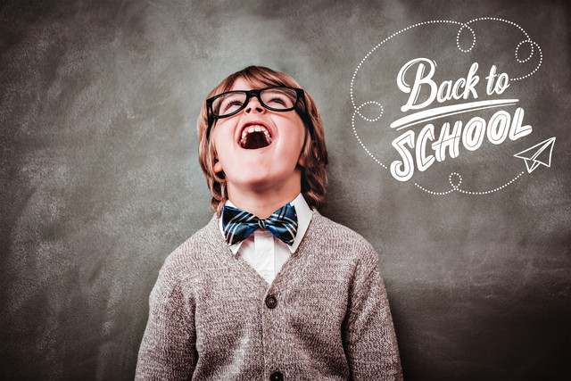 back-to-school-against-boy-laughing-in-front-of-blackboard
