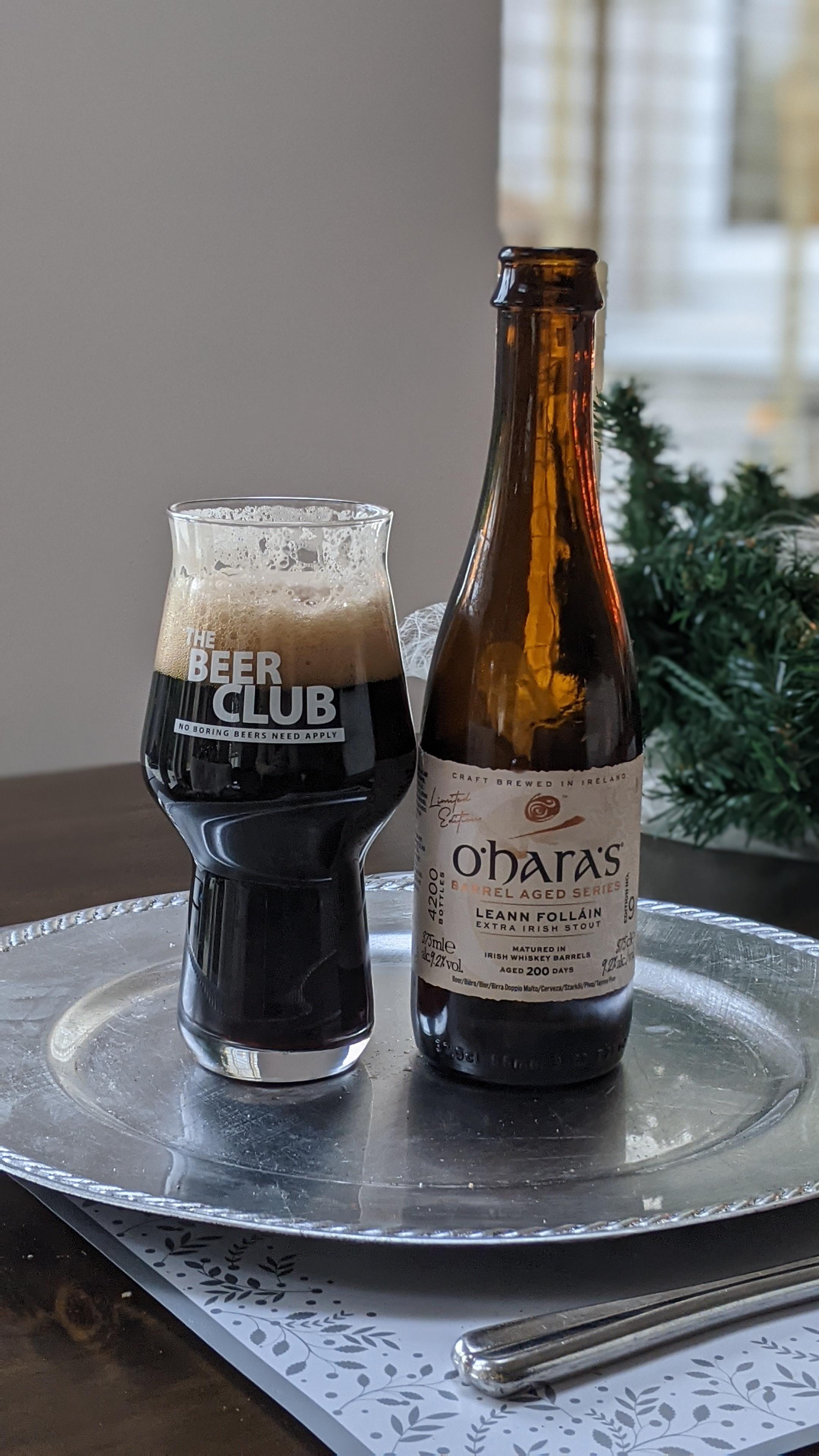 dark stout with good white head, bottle beside it