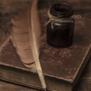 Vintage-old-books-scrolls-feather-pen-and-inkwell-on-wooden-table