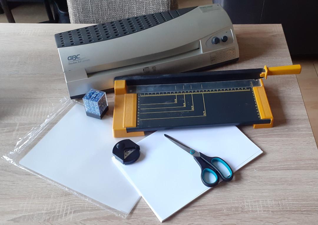 Naast de printer gebruik ik dit: een lamineermachine met lamineerbladen, een snijmachine, een schaar, een hoekenknipper, papier en wat dobbelstenen.