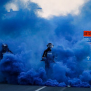 Police-in-riot-gear-walk-through-a-cloud-of-blue-smoke-as-they-advance-on-protesters-near-the-Minnea