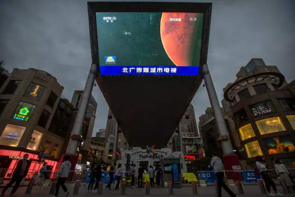 A Chinese state media broadcast of a news report about the country's successful landing of a probe on Mars is shown on a large video screen at a shopping mall in Beijing on May 15, 2021.