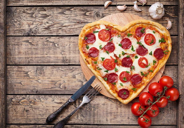 Heart-shaped-pizza-with-pepperoni-tomatoes-and-mozzarella-on-vintage-wooden-table-background-Valenti