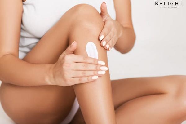 Woman-applying-moisturizer-cream-on-her-legs-white-studio-background