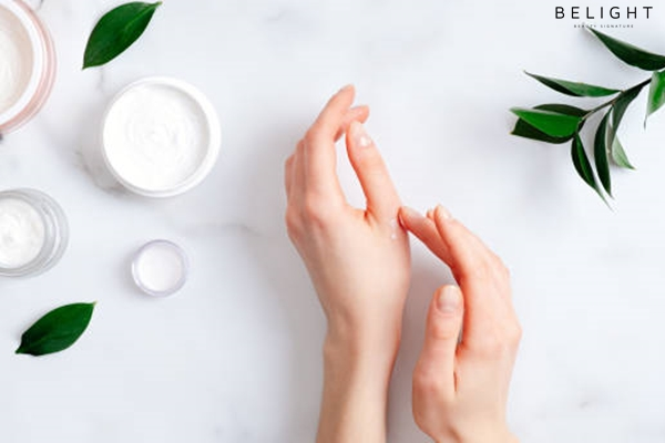 Cosmetic-cream-on-female-hands-jars-with-milk-swirl-cream-and-green-leaves-on-white-marble-table-Fla